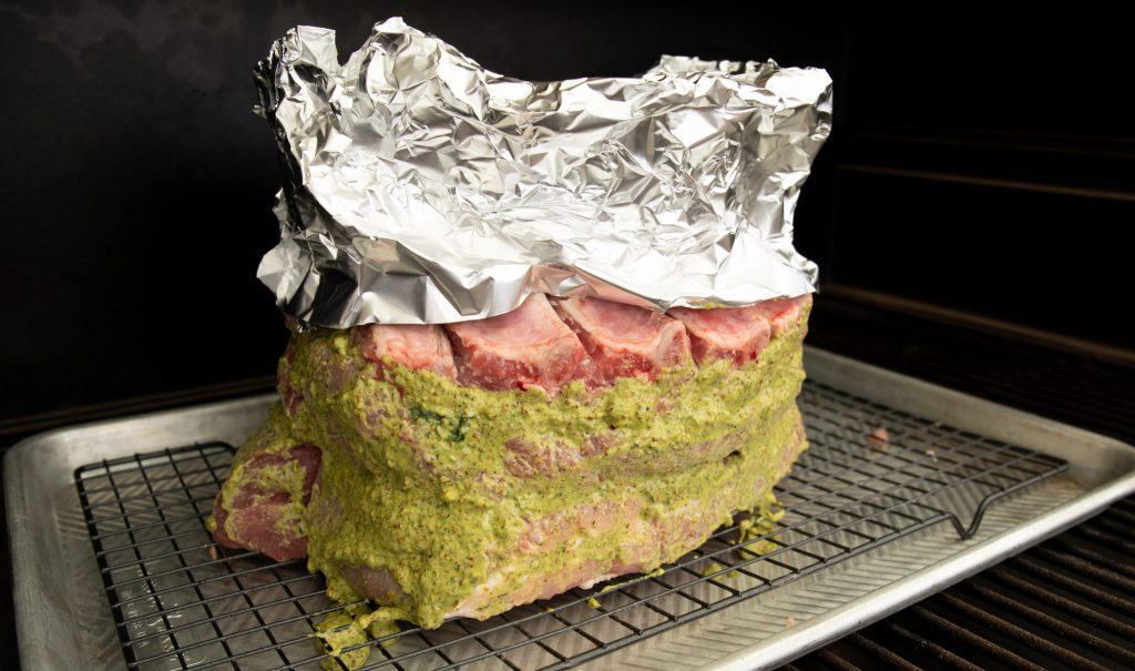 Pork Crown Roast on a rack inside of a smoker with foil covering the bones and an herb paste on the meat.