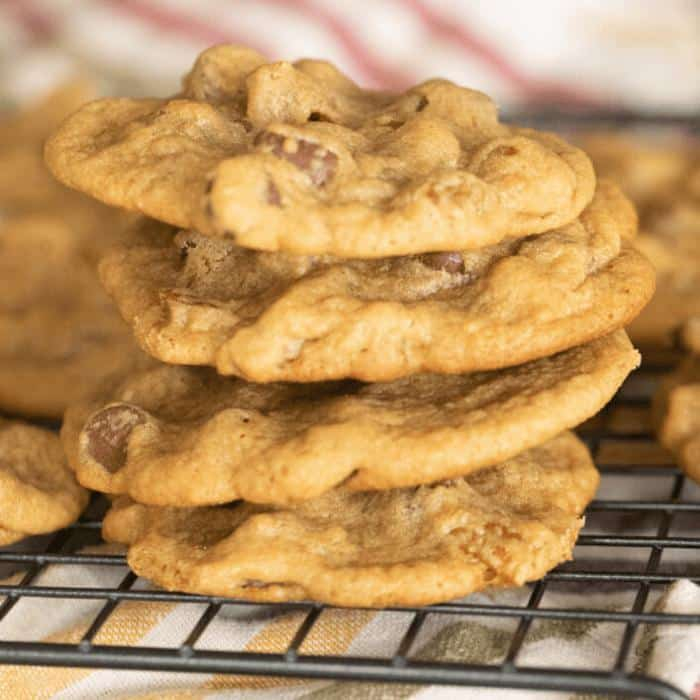 Four smoked chocolate chip cookies stacked on a metal cooling rack.