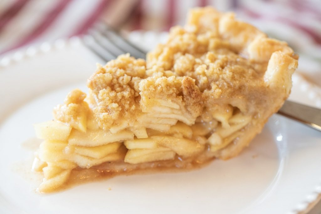 A slice of Dutch apple pie on a white plate