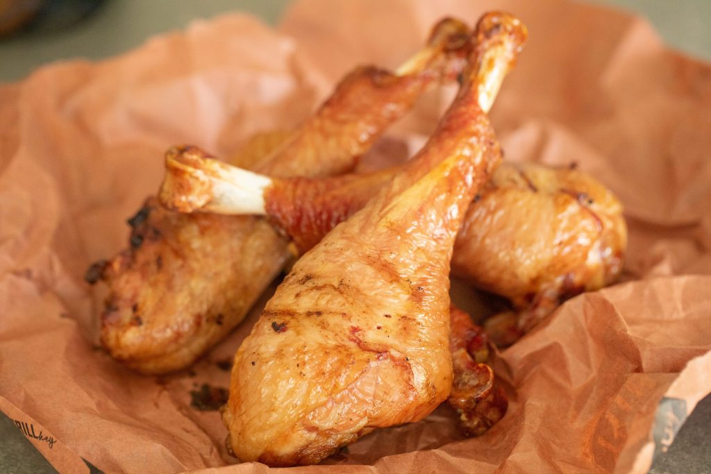 Four smoked turkey legs in a pile on crumpled butcher paper.