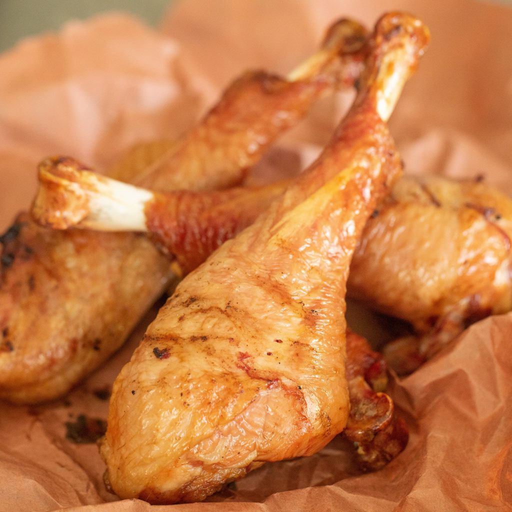 smoked turkey legs in a pile on butcher paper.