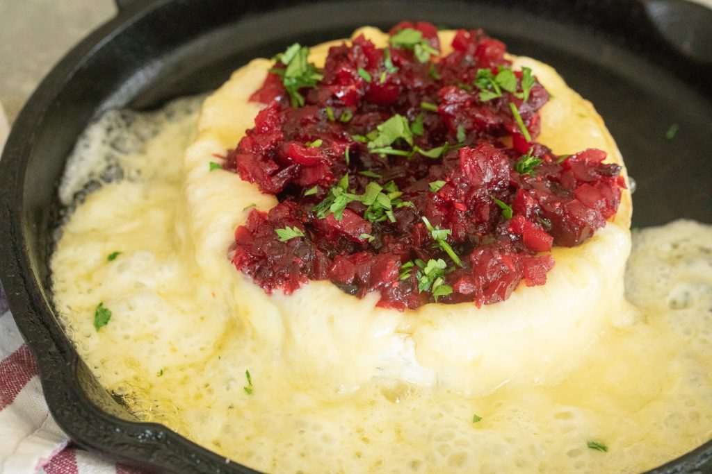 Grilled brie in a cast iron skillet that is all melty topped with cranberry jalapeno relish.