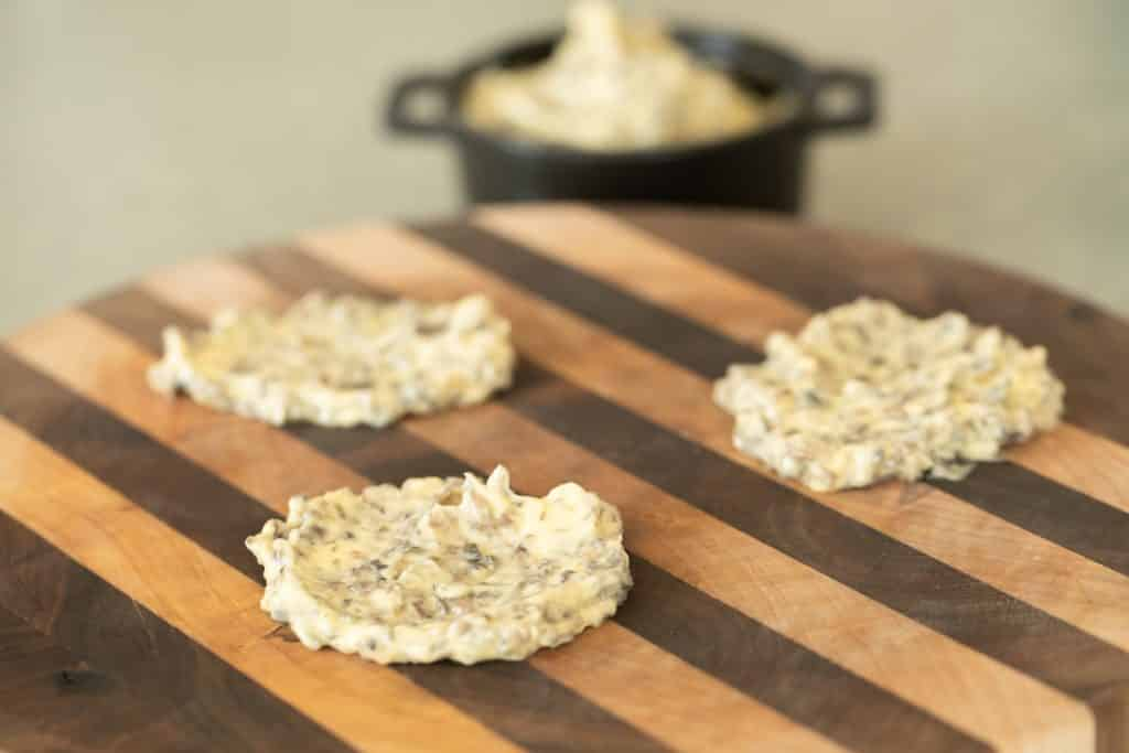 three slabs of mushroom resting butter on a circular wooden board for grilled filet mignon.