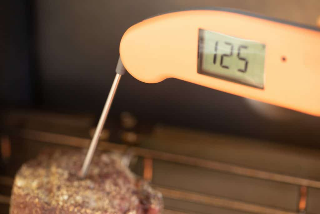 meat thermometer probe in a grilled filet mignon showing a temperature of 125 degrees F.