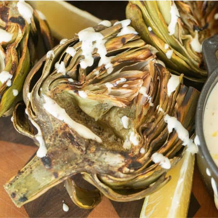 grilled artichoke halves on a wooden board drizzled with lemon garlic aioli