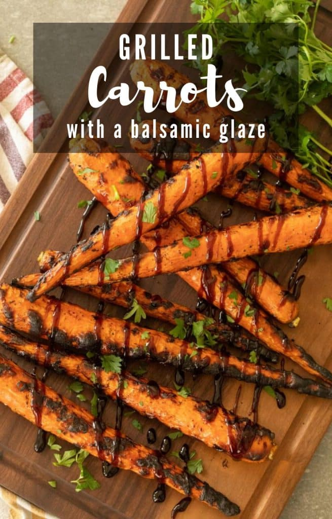 grilled carrots drizzled with balsamic glaze on top of a wooden cutting board.