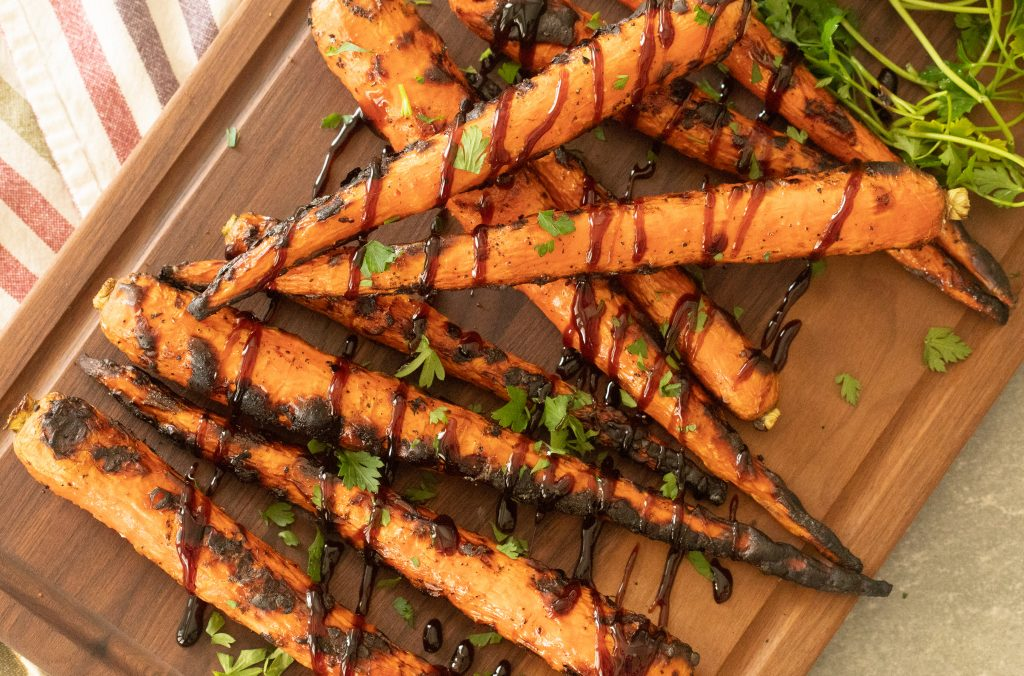 grilled carrots on a wooden cutting board drizzled with balsamic glaze.