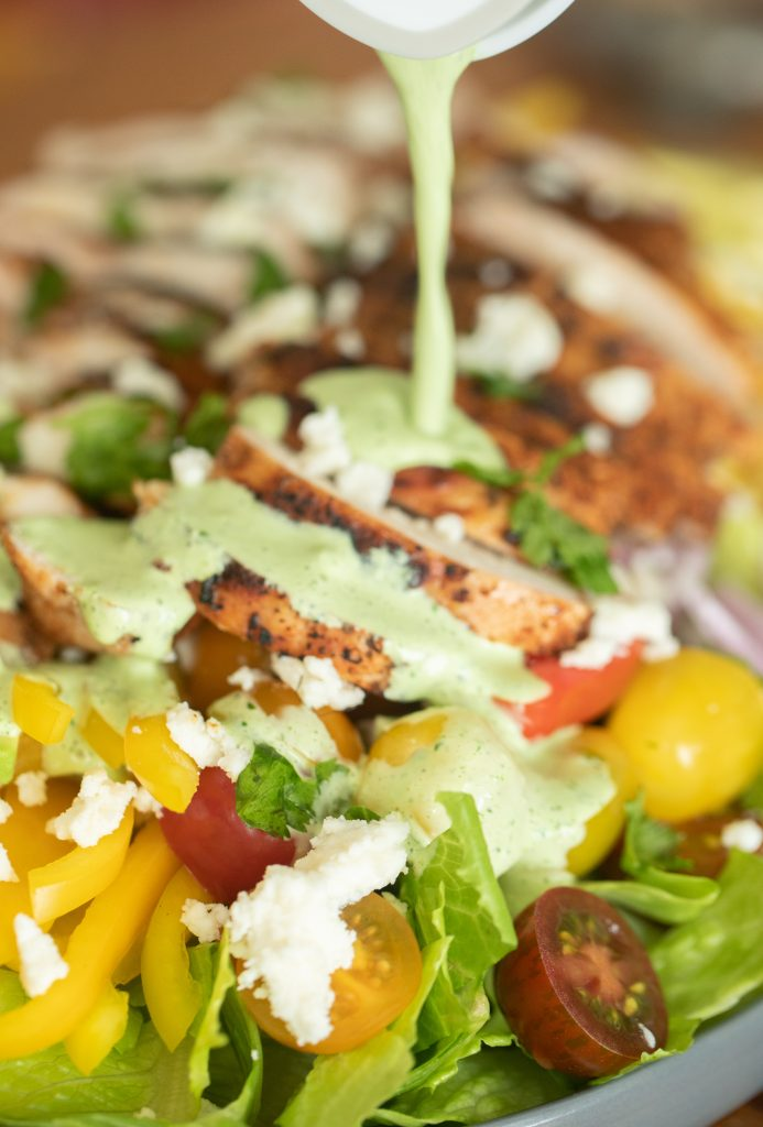 jalapeno lime salad dressing being poured on top of a grilled chicken salad.