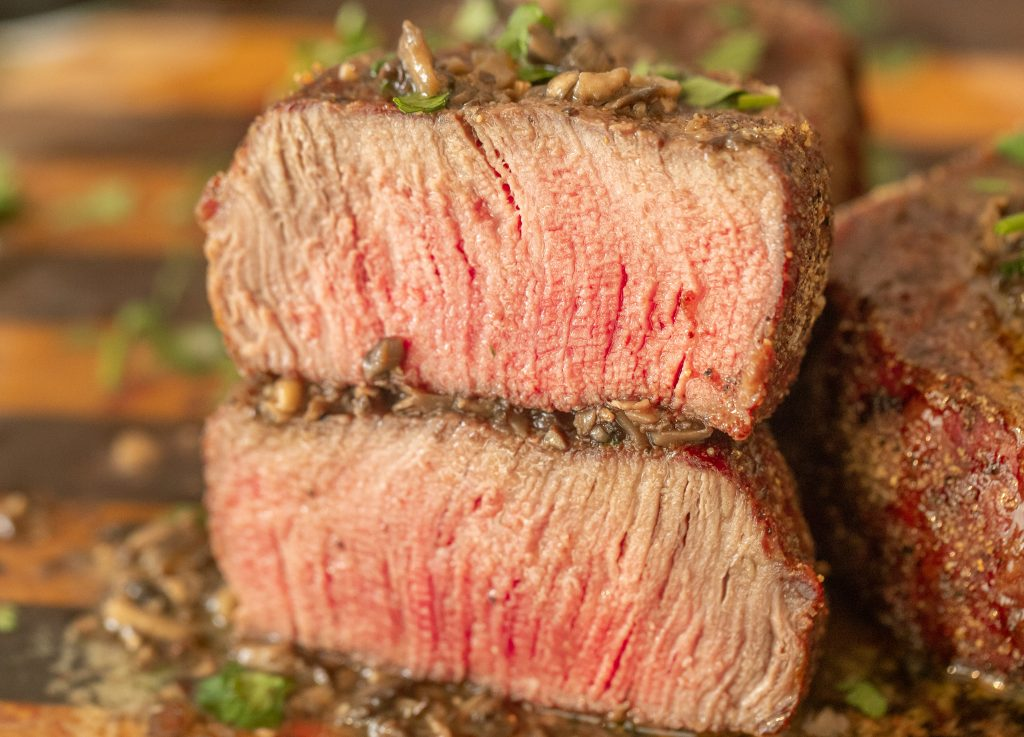 two slices of grilled filet mignon stacked with mushroom resting butter melted on top and underneath.