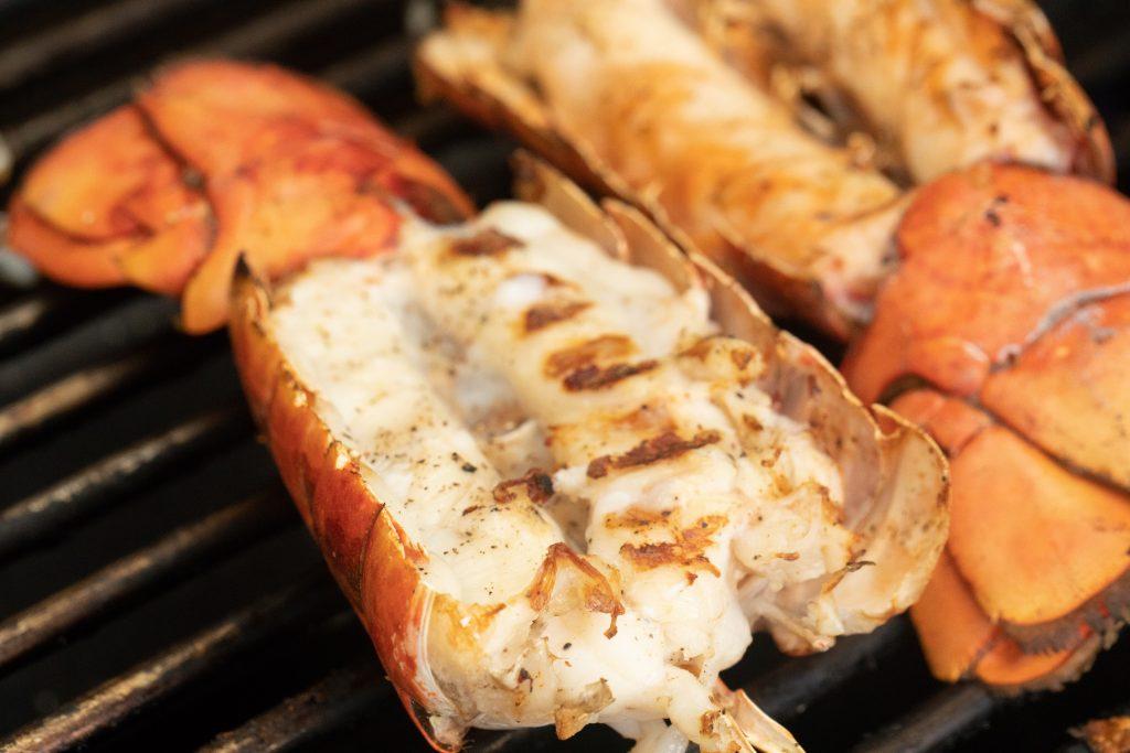 lobster tail halves split open on the grill.