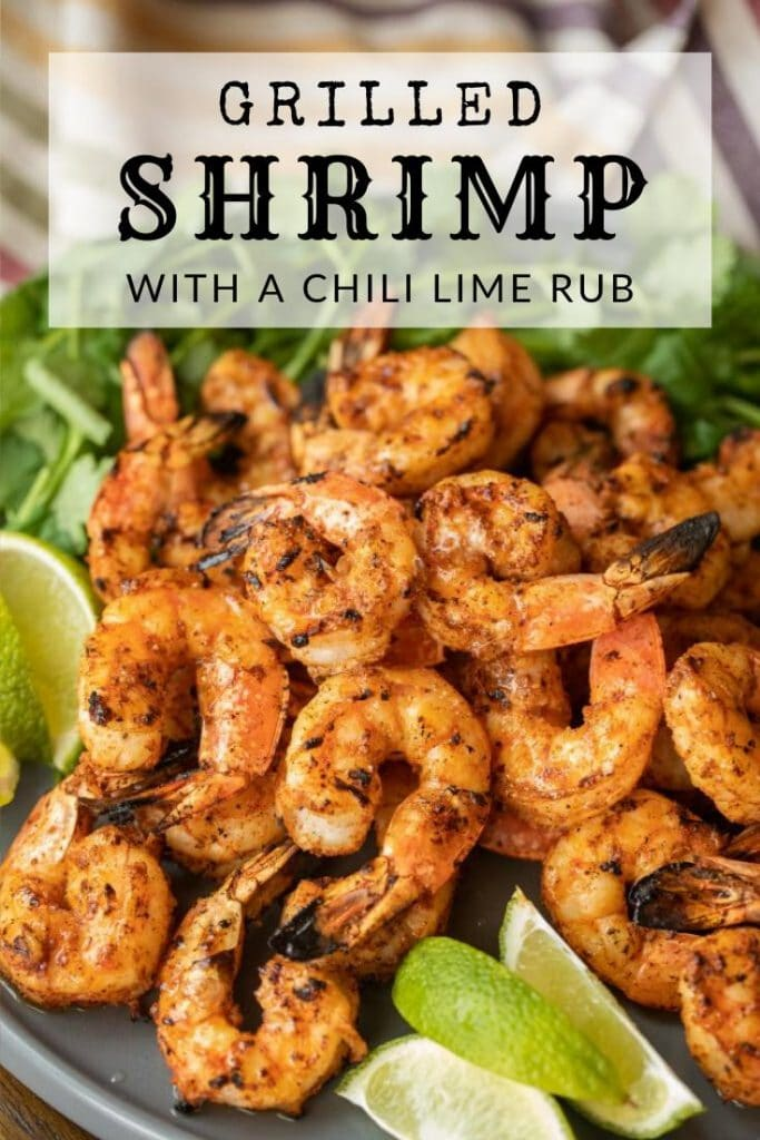 grilled shrimp with a chili lime rub on a plate next to lime wedges and fresh herbs.