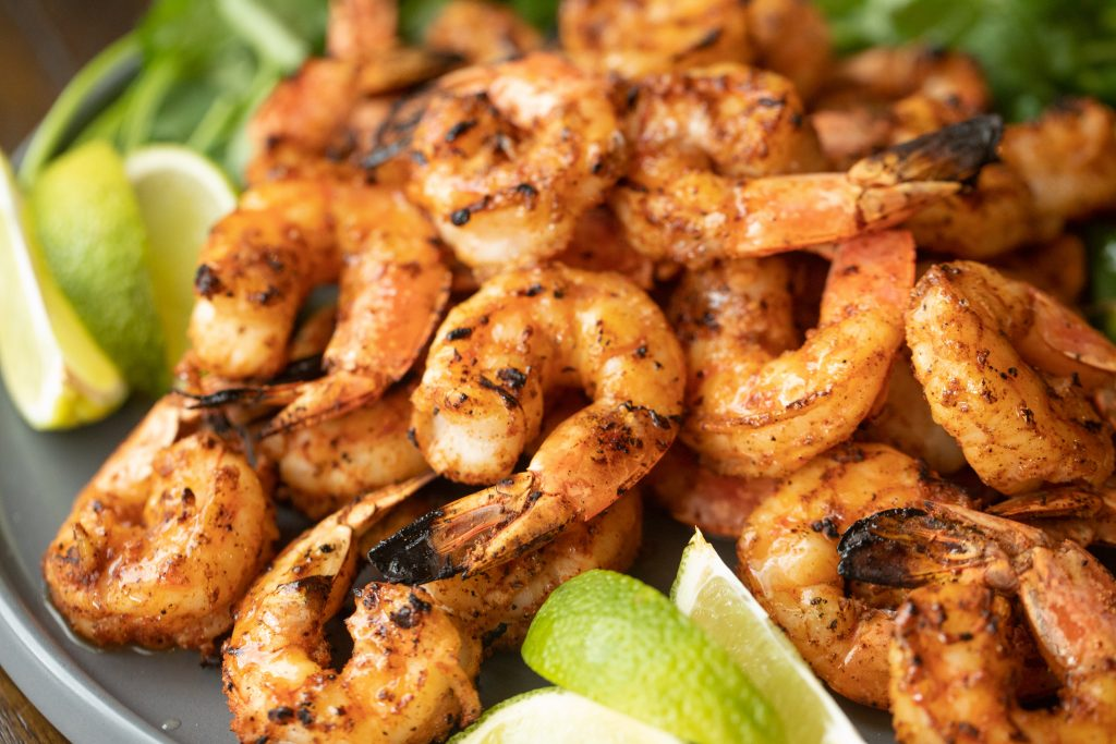 plate of seasoned and grilled shrimp with lime wedges.