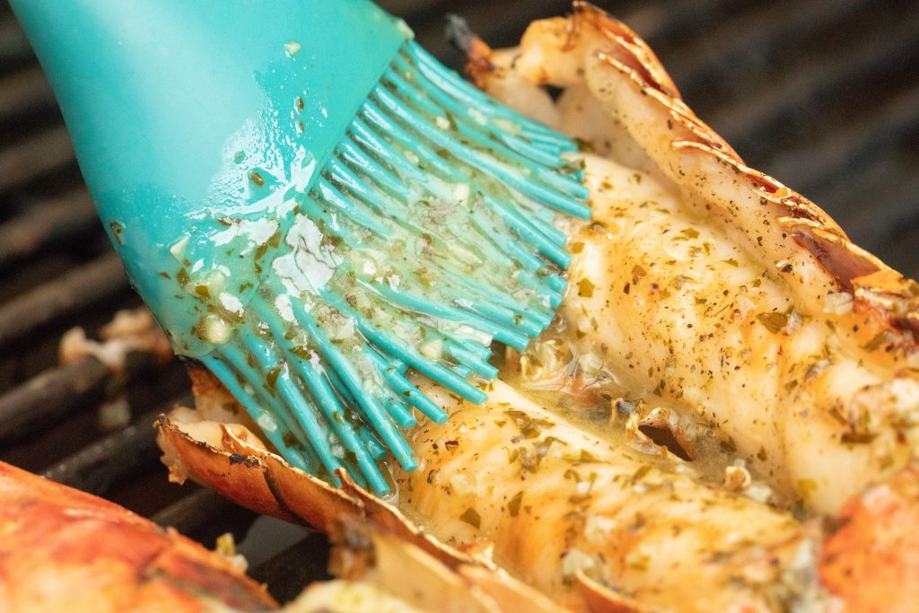 silicon basting brush brushing lemon garlic butter on a lobster tail on a grill.