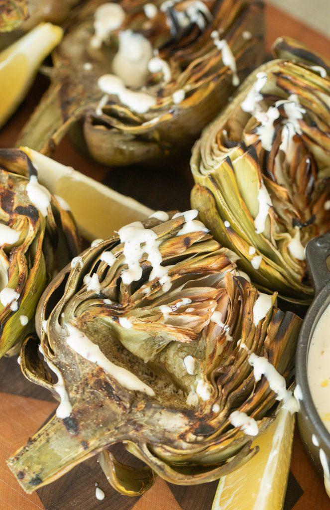 Grilled artichoke halves with lemon garlic aioli next to lemon wedges.