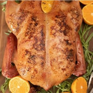Whole smoked duck surrounded by fresh herbs and orange halves.