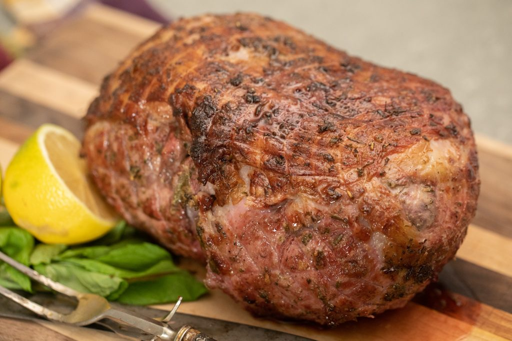 whole marinated and smoked leg of lamb on a wooden cutting board next to a half a lemon, fresh herbs, a knife and a fork