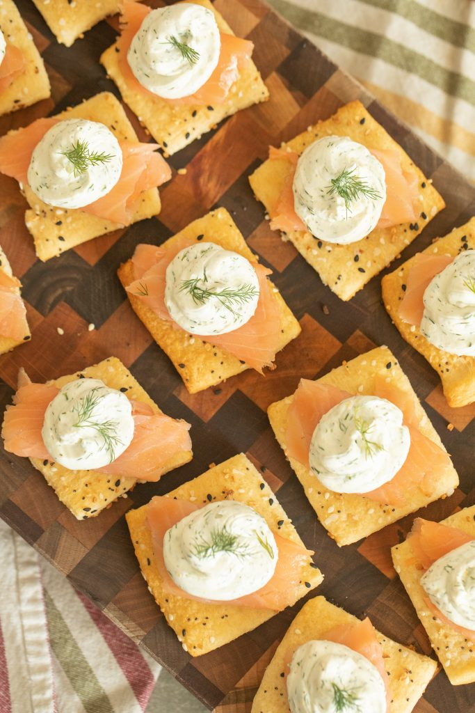 wooden cutting board arranged with a dozen smoked salmon appetizers.