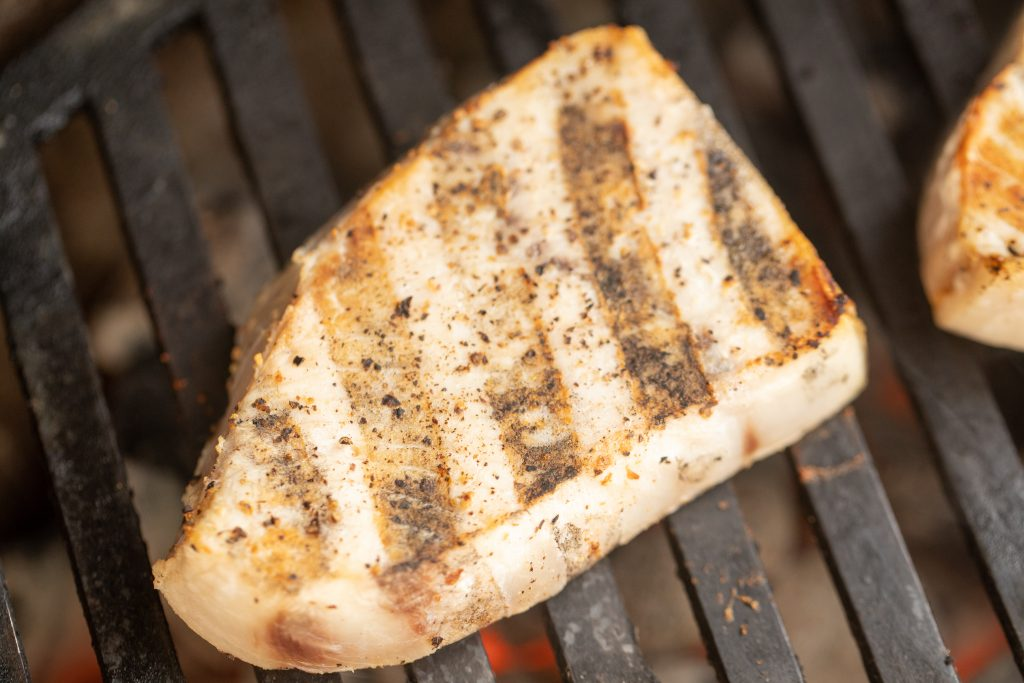 seasoned swordfish on the grill with hot charcoal under the grates.
