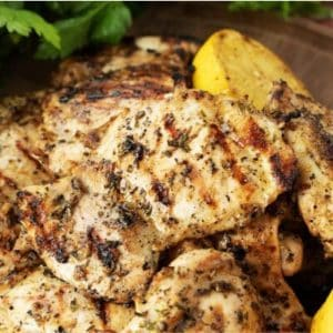 Grilled chicken thighs stacked on a wooden plate with lemon halves.