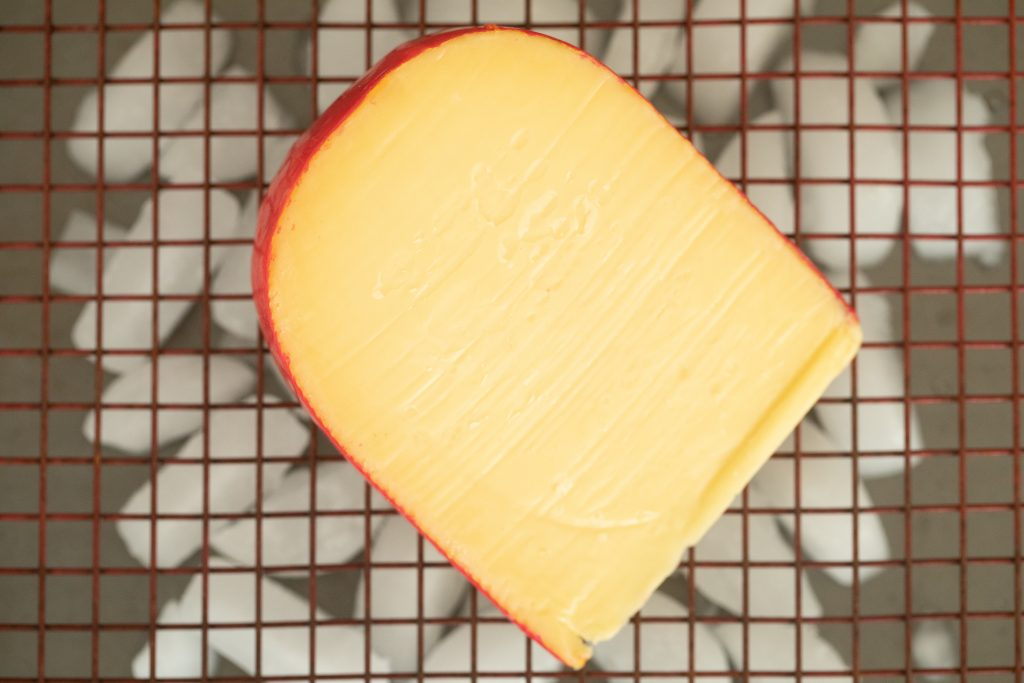 gouda cheese on a baking rack over a baking sheet filled with ice.