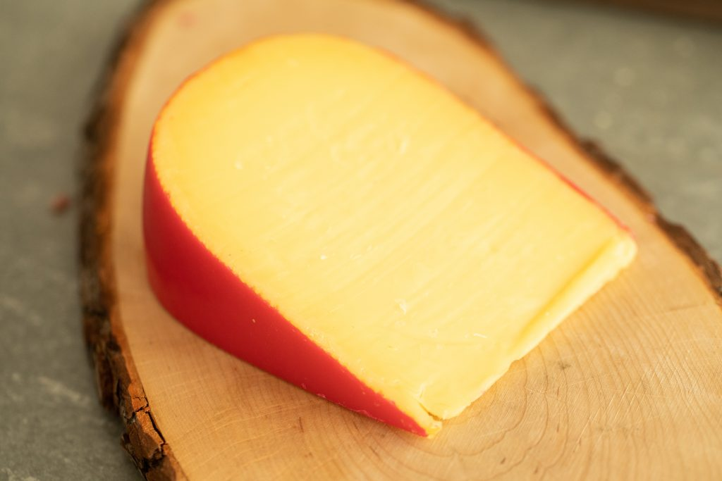 smoked gouda cheese on a wooden cutting board.