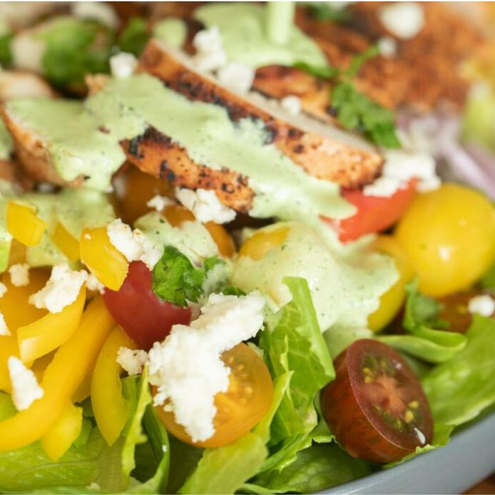 Chopped lettuce topped with sliced tomatoes, yellow bell peppers, sliced chicken breast, and dressing