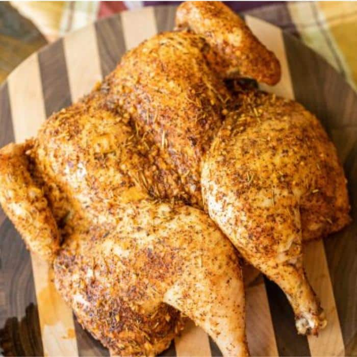 whole cooked chicken, covered with seasoning and resting on a wooden cutting board.