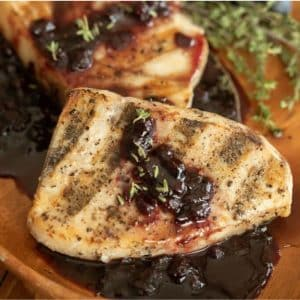 Two whole grilled swordfish fillets drizzled with a blueberry balsamic reduction.