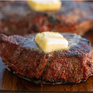 Close up of a pad of butter melting on a whole grilled steak.