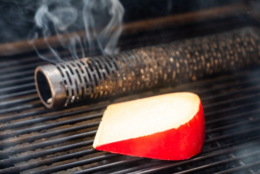gouda cheese on the grill grates of a smoker next to a smoke tube.