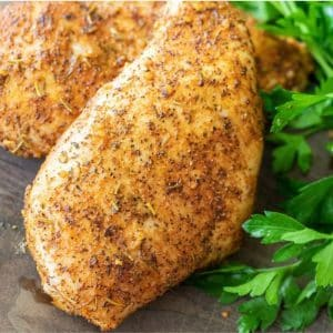 Two seasoned smoked chicken breasts on a wooden board next to fresh herbs.