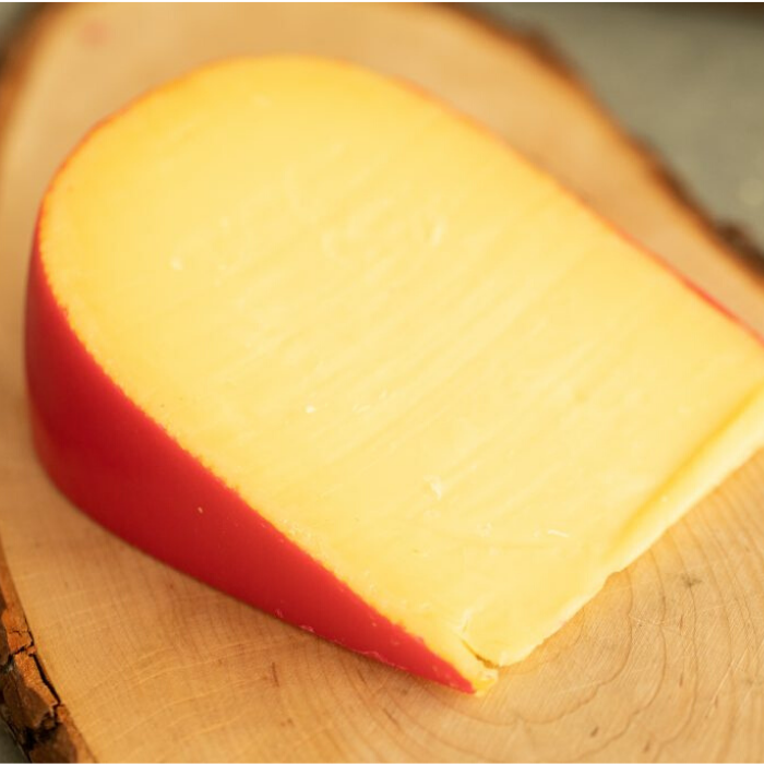 Wedge of smoked gouda on a wooden board.