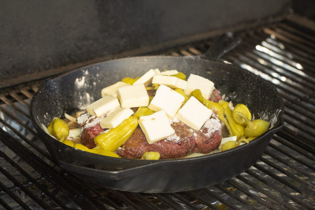 ingredients for mississippi pot roast in a cast iron skillet on grill grates on the smoker