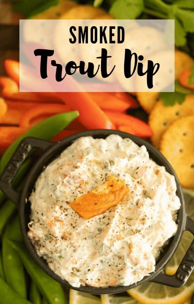 container of smoked trout dip surrounded by fresh sliced vegetables and crackers.