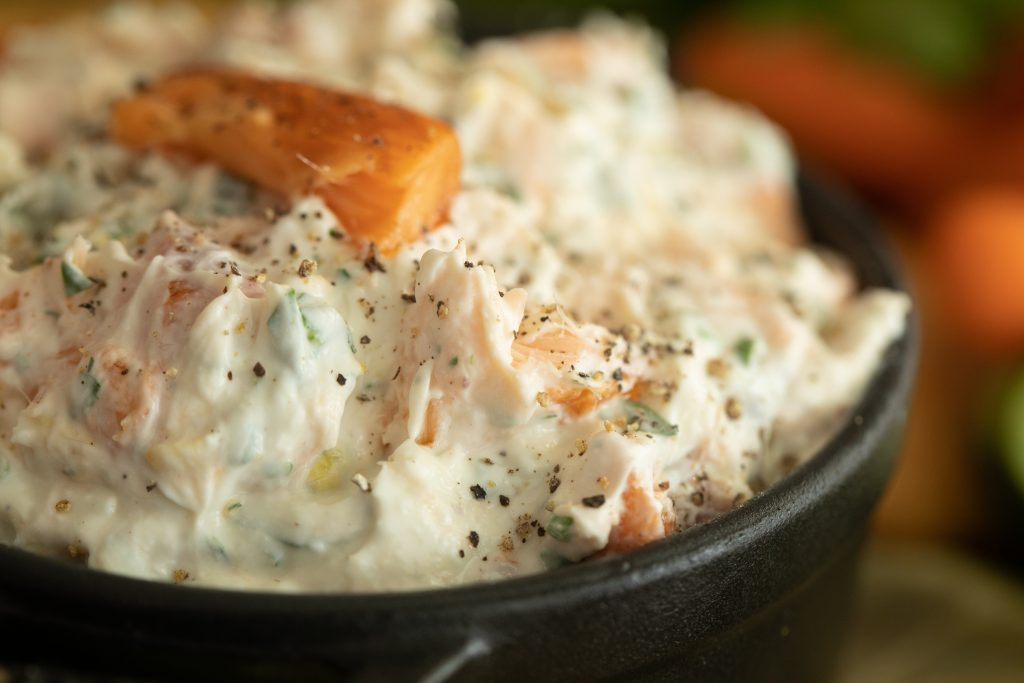 close up of smoked trout dip in a black serving dish.