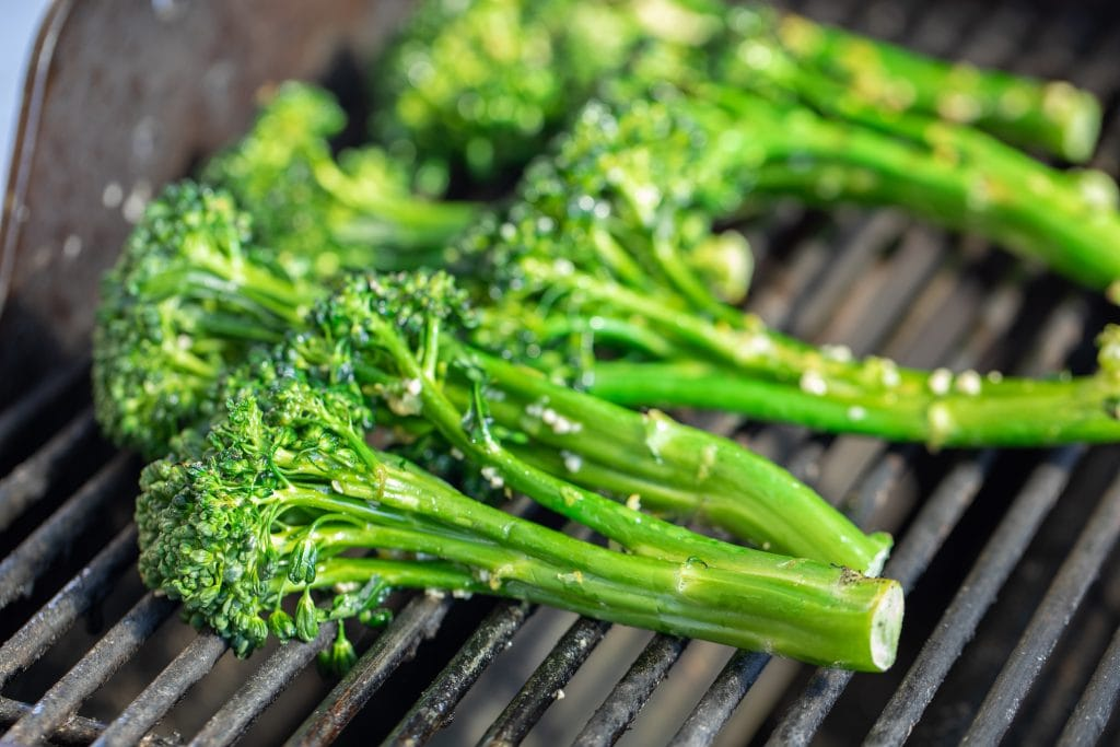 Close up of seasoned broccolini on the grates of a gas grill.