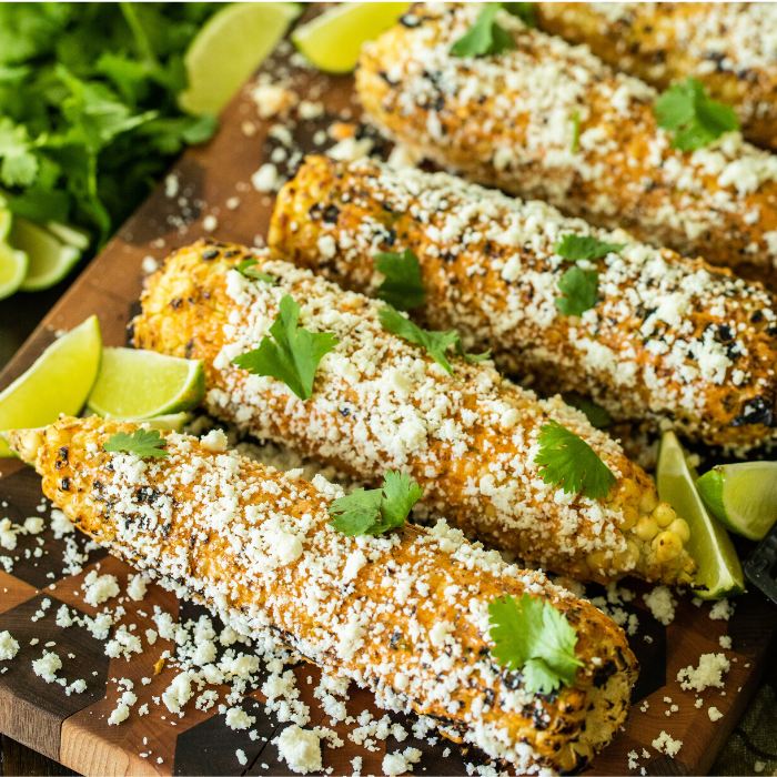 row of Mexican street corn on a wooden cutting board