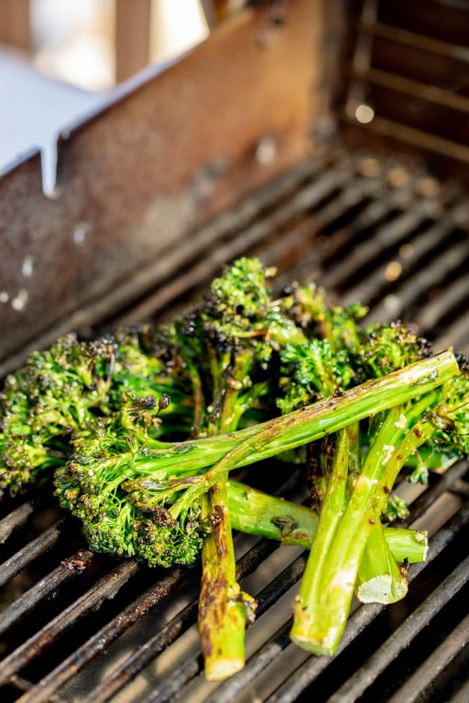 Grilled broccolini piled on the grill grates of a gas grill.
