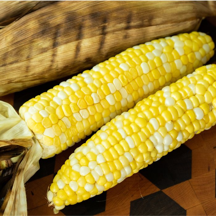 two ears of grilled corn on a wooden cutting board