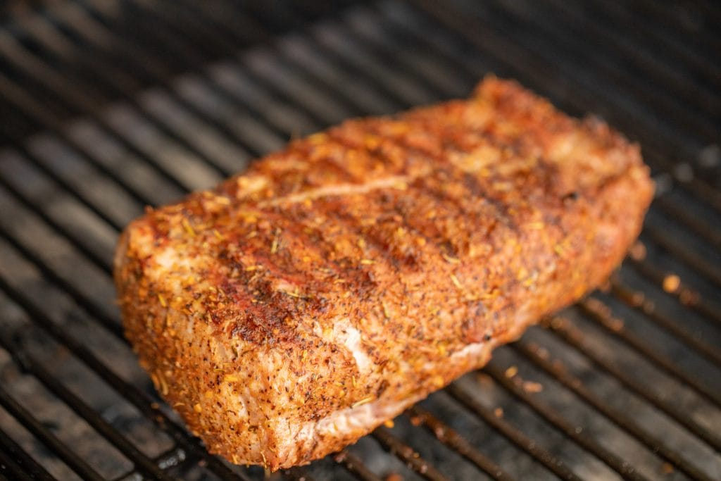 grilled pork loin roast on the grill grates of a charcoal grill.