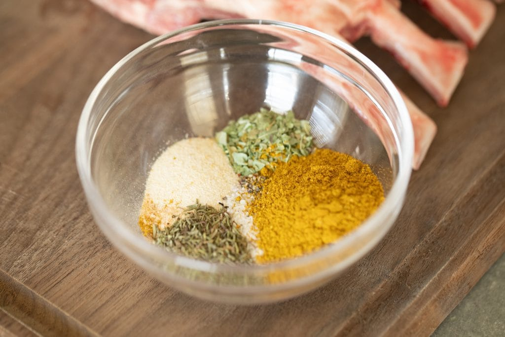 Each of the spices in the recipe unmixed in small glass bowl next to a partially showing raw rack of lamb. All on a wood cutting board.