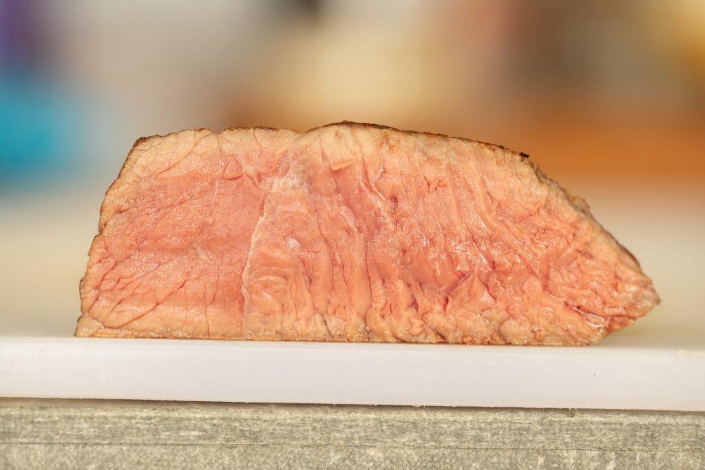 Cross section image of medium rare steak on a cutting board.