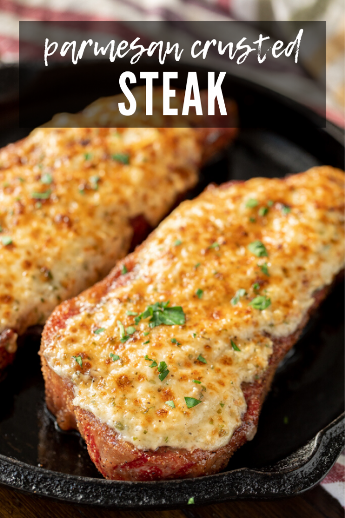 two whole parmesan crusted steaks in a cast iron skillet.