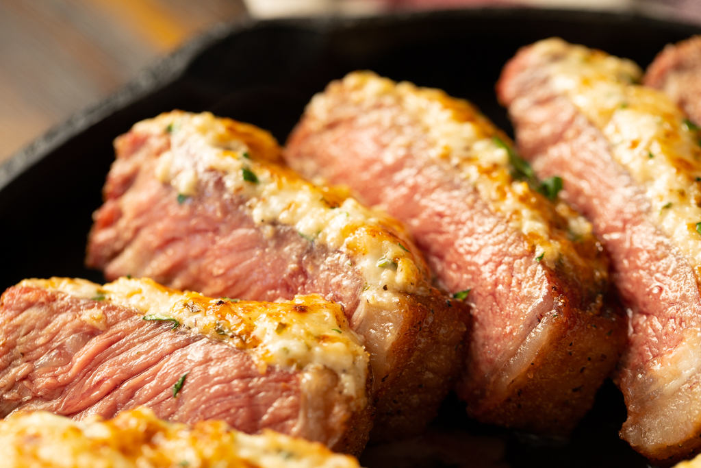 Sliced parmesan crusted steak in a cast iron skillet.