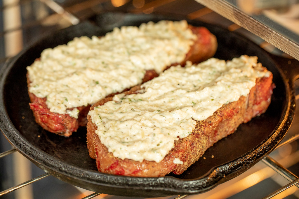 two smoked NY strip steaks covered in Parmesan in a cast iron skillet.