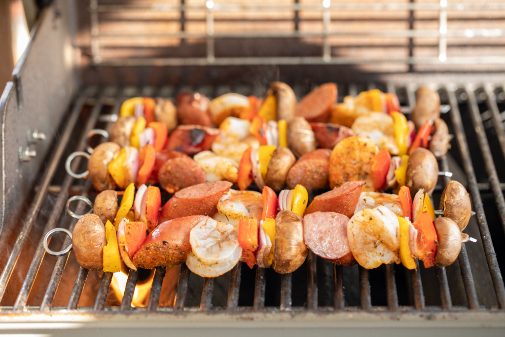 5 shrimp and sausage kabobs on a gas grill.