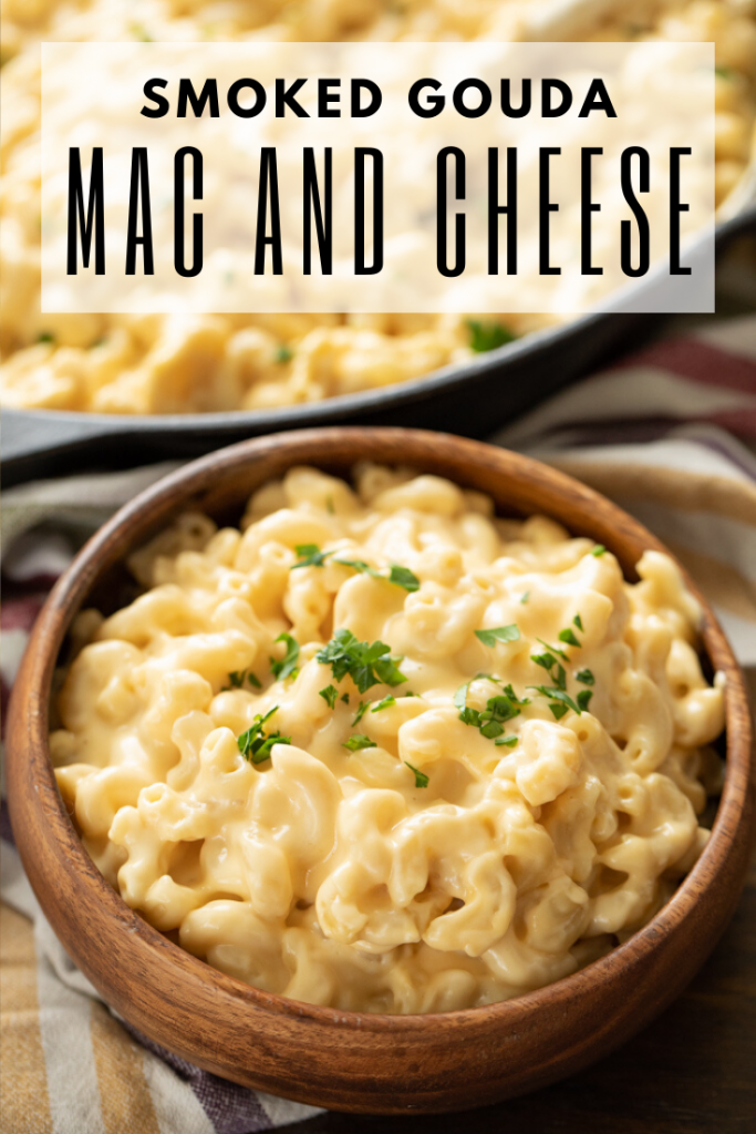 wooden bowl of smoked gouda mac and cheese topped with fresh herbs.