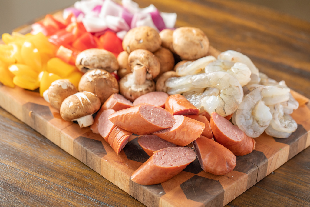 chopped bell peppers, onions, mushrooms, shrimp, and smoked sausage on a wooden cutting board.
