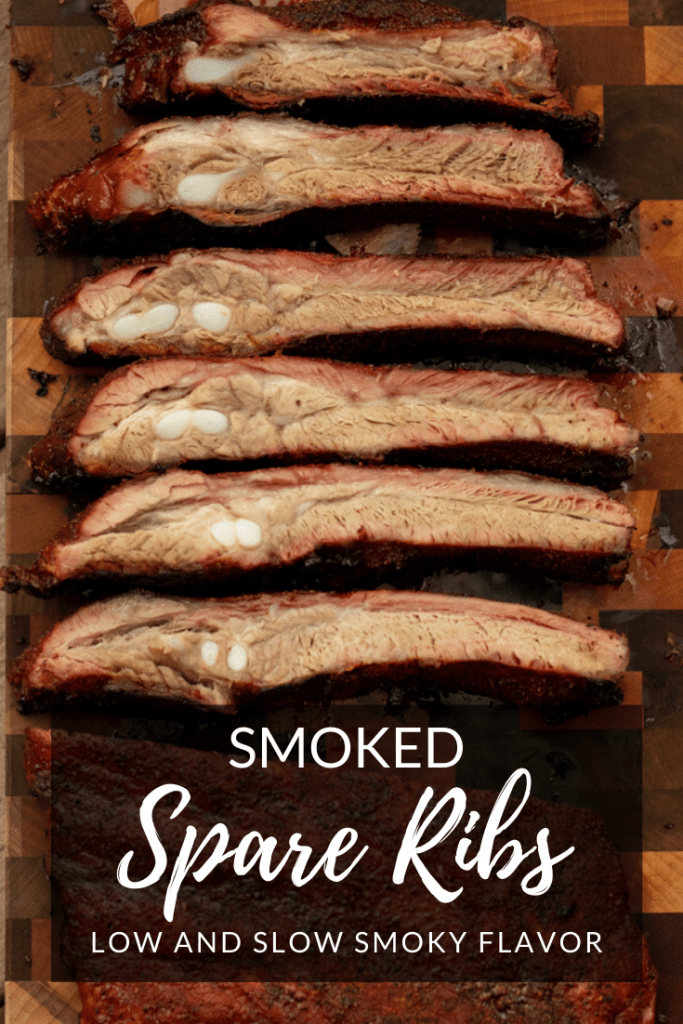 smoked spare ribs in a line on a wooden cutting board.