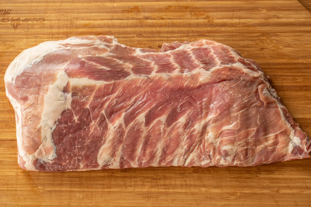 Raw rack of spare ribs on a cutting board